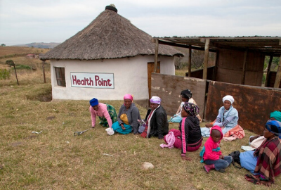 Women wait on the ground for a 'clinic' in the Eastern Cape