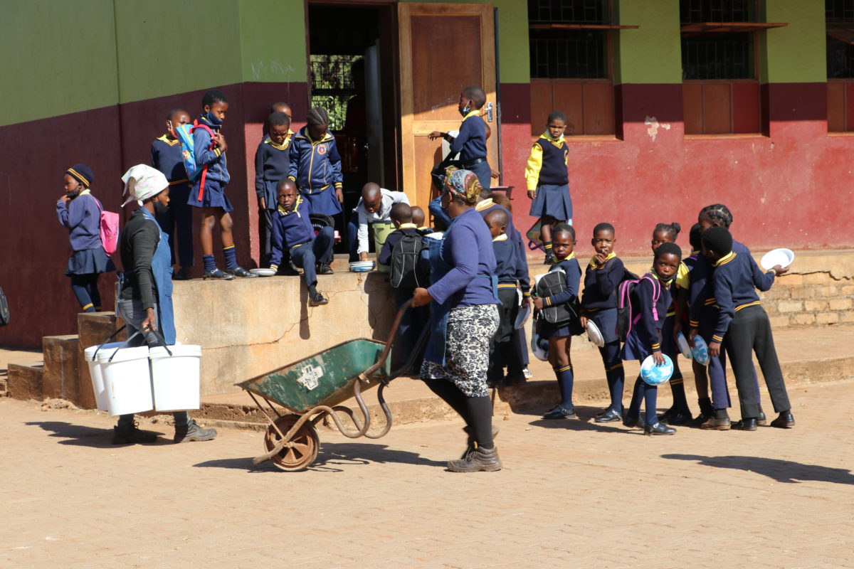 Primary school learners queue for a school meal in Giyani, Limpopo. Voluntary food handlers bring food in large buckets and a wheelbarrow.